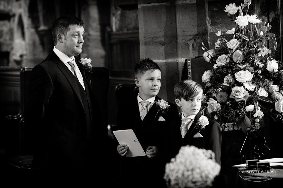 groom and sons looking thoughtful watching bride walking into weston on trent church wedding