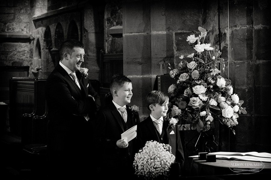 groom and sons smiling seeing bride walk into church