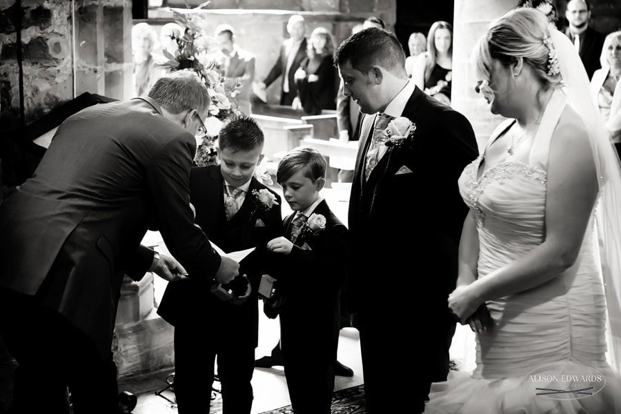 young boys giving rings to vicar in church
