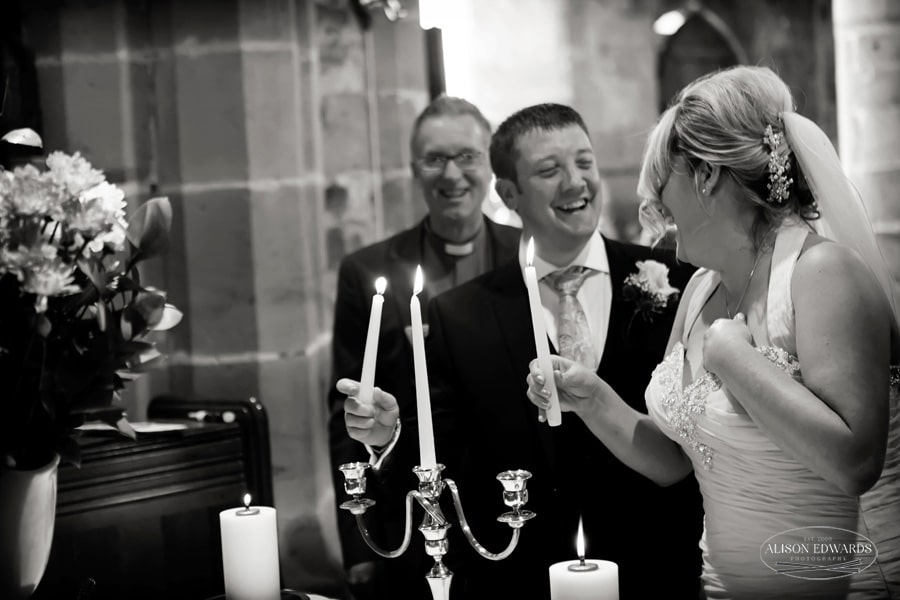 bride and groom laughing in church with candles