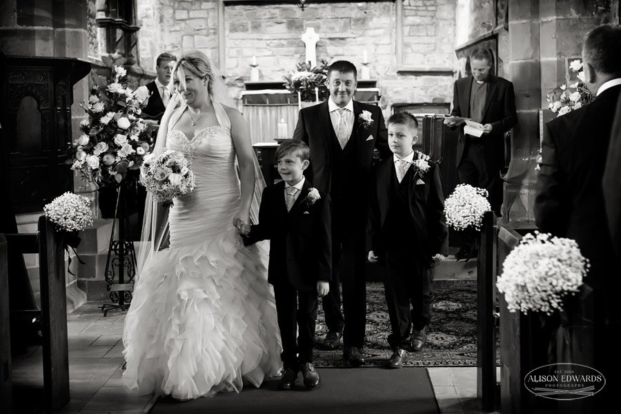 bride groom and sons walking out of church