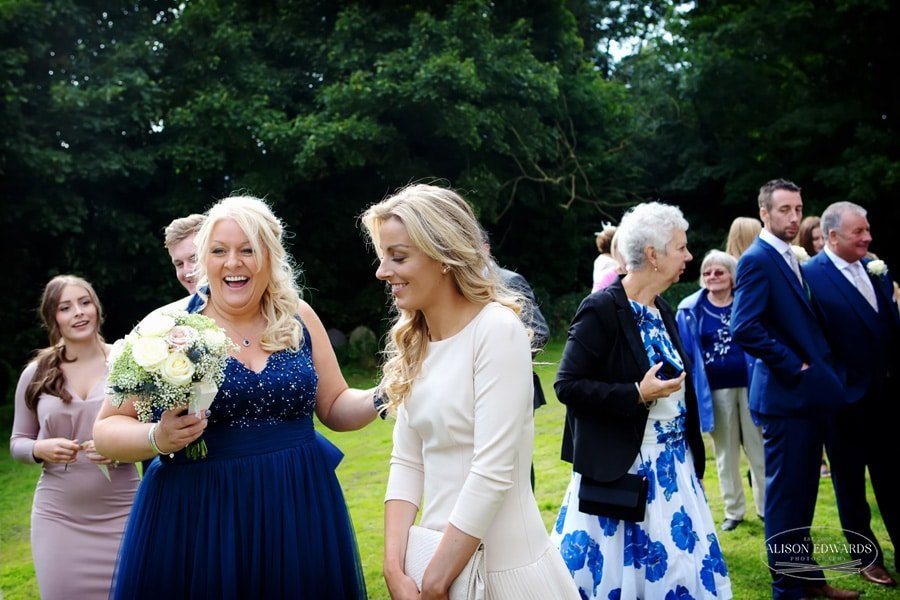 wedding guests laughing outside of church