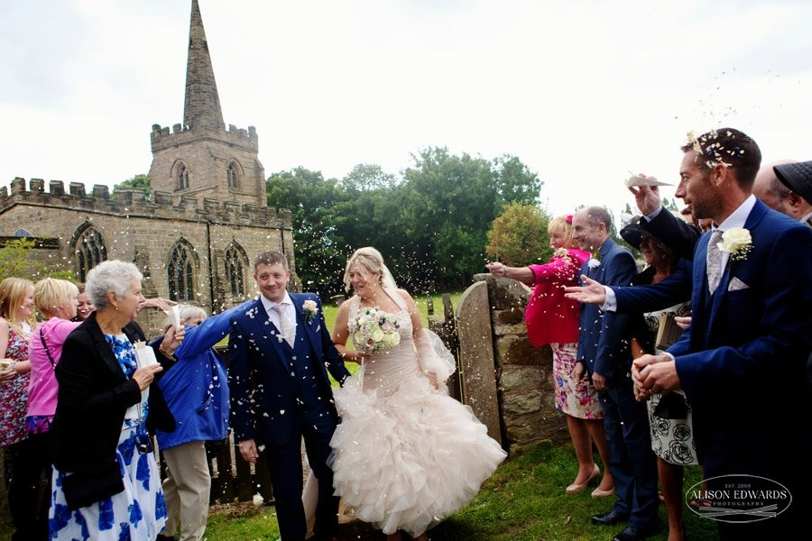 guests throwing confetti on bride and groom at weston on trent church wedding